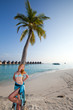 Young beautiful woman stands near palm tree, Maldives
