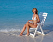 Young pretty woman in a beach chair at ocean..