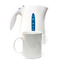 tea kettle on a white background and a mug in focus