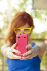 Hipster girl taking photo with her pink smart phone