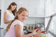 Girl helping mother to prepare food in kitchen
