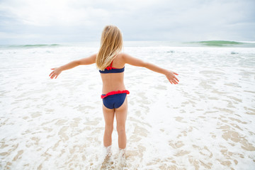 Young girl standing in water at beach