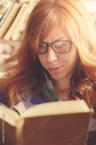 Hipster girl reading a book. Retro styled imagery, grainy