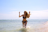 Beautiful young woman running by tropical sea