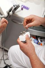 Fußpfleger nimmt Polieraufsatz aus einer Box