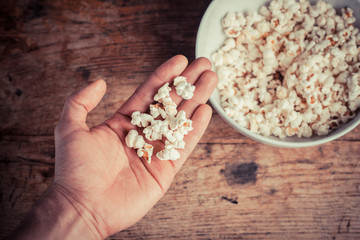 Hand getting popcorn from bowl
