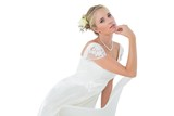 Confident bride with hand on chin leaning on chair