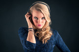 Beautiful blonde woman listening to music with earphones against