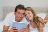 Smiling couple using digital tablet in bed