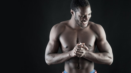 Confident young smiling man shirtless portrait against black bac