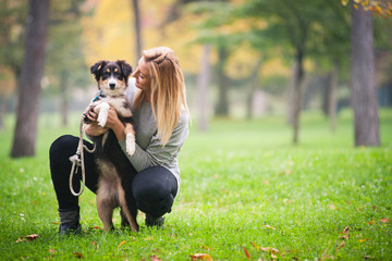 Young woman playing with Australian Shepherd dog outdoors in the