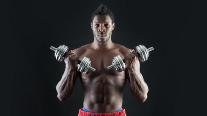 Confident young man shirtless portrait training with dumb-bells
