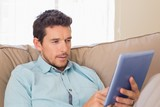 Relaxed man using digital tablet on couch