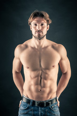 Portrait of confident young man shirtless against black backgrou