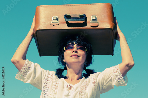 beautiful 50 years old woman with vintage bag outdoors