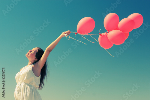 young woman holding red balloons - 62256174