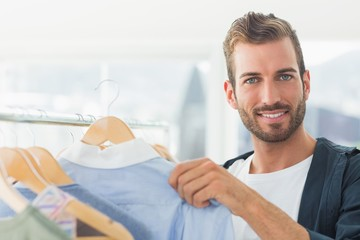 Handsome male customer by clothes rack