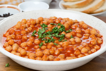 chickpeas in tomato sauce with fresh herbs, close-up