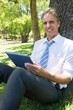 Confident businessman with digital tablet in park