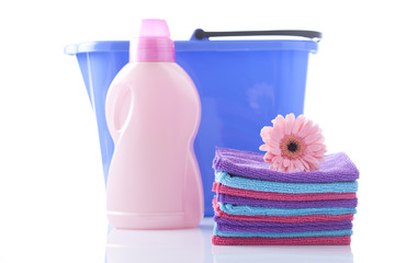 Detergents and towels before plastic basket isolated on white