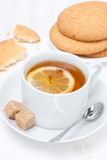 fragrant black tea with lemon and cookies, vertical