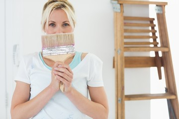Woman holding paint brush in front of face at the new house
