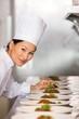 Smiling female chef garnishing food in kitchen