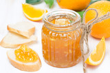 orange jam in a glass jar and fresh bread