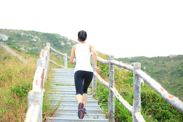 fitness woman running up on mountain stairs to peak