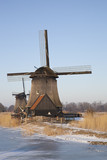 Two classic windmills in winter with blue sky
