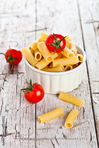 uncooked pasta and cherry tomatoes in a bowl