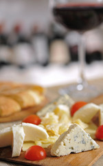 Cheese plate and red wine on wooden table