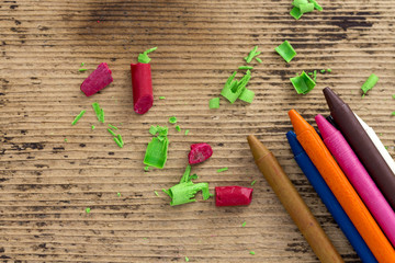 Colorful crayons on wooden background
