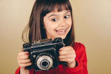 Funny little retro photographer girl