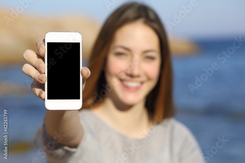 Happy woman showing a smart phone display on the beach