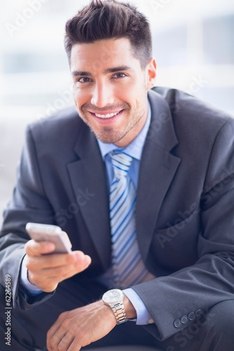 Happy businessman sitting on sofa sending a text