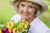 Close-up of smiling mature woman holding flowers at park