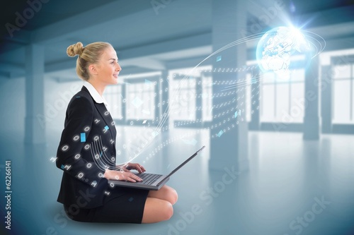 Blonde businesswoman sitting using laptop with interface
