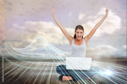 Cheering blonde using laptop with clouds