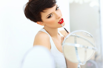 Beautiful Brunette applies lipstick.  Red lips. Make up
