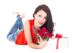 beautiful woman lying with gift box and flowers isolated on whit