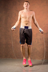 Young boxer training with a skipping rope