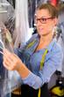 Textilreinigerin  in Wäscherei kontrolliert Kleidung