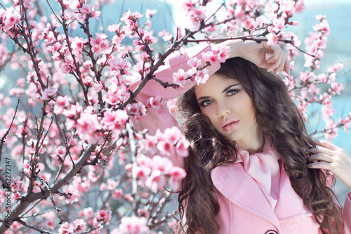 Portrait of Beautiful woman posing over Pink Spring Cherry bloss