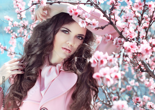 Beautiful brunette girl posing over Pink Spring Cherry blossoms.