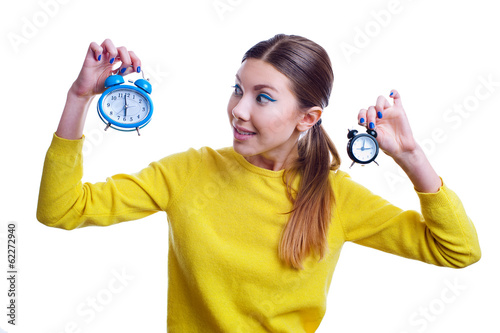 Young beautiful woman holding big and small clocks with surprise