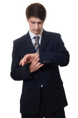 The businessman in a business suit looks at watch