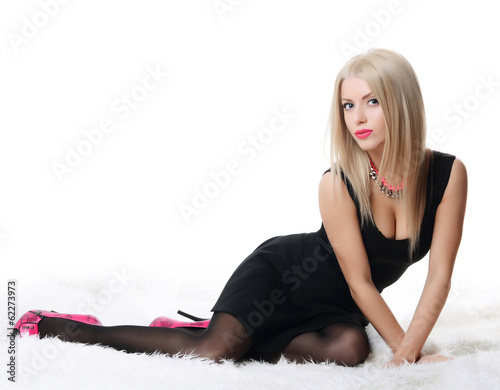 Beautiful sensual woman in a black dress on a carpet