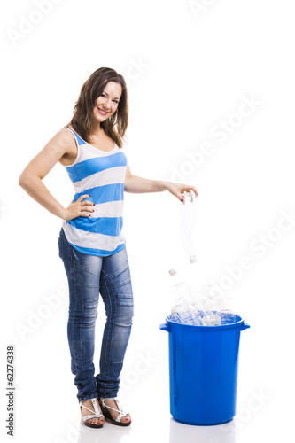 Beautiful young woman putting  a bottle on a recycle contentor