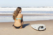 Teenage surfer girl sitting on the beach and checking the waves